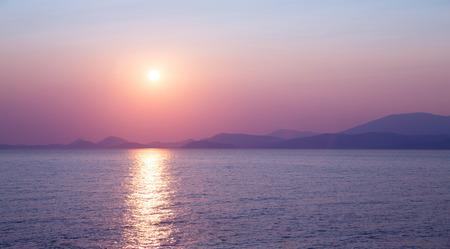 Beautiful purple sunset on the sea, sun reflection on peaceful water, wonderful landscape, scene destination, beauty of nature concept photo