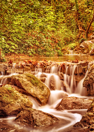 Waterfall in the autumn park, little mountainous wild river streaming in the forest, beauty of nature concept Stock Photo