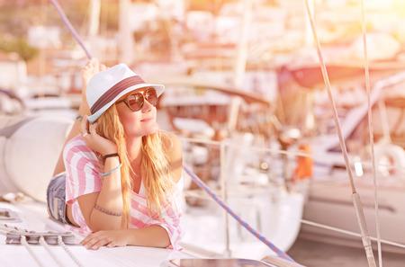Happy blond female lying down on sailboat and enjoying beautiful sunset photo