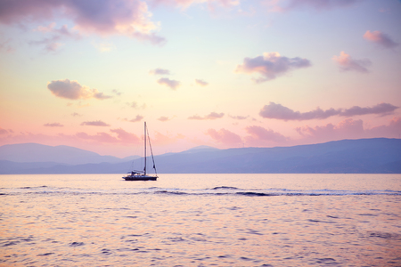 yachting: Luxury sailboat in beautiful pink sunset light on the sea, amazing view, luxury water transport, summer vacation concept