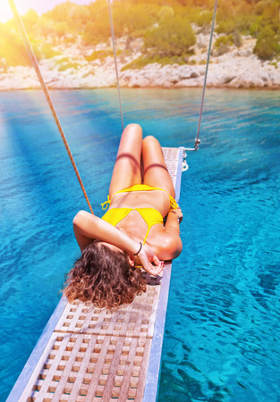 Sexy woman tanning on sailboat, female relaxing above transparent blue sea, girl enjoying bright sun light, active lifestyle, happy summer vacation photo