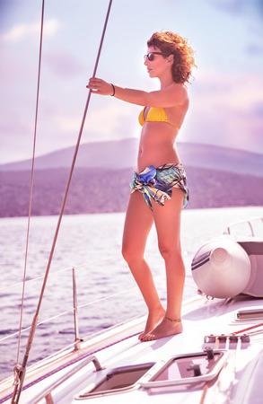 Beautiful slim female standing on the deck of yacht and enjoying beautiful sunset, active summer adventure, luxury sea cruise photo