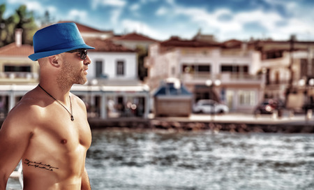 Handsome man with tattoo enjoying cityscape on seashore, traveling on yacht along beautiful Europe, guy with fit sexy body modeling,  summer vacation concept photo