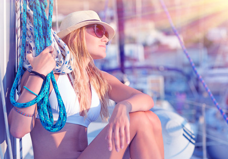 Young sexy sailor girl relaxing on sailboat, holding rope, enjoying sea cruise, active lifestyle, female in mild sunset light, summer vacation concept photo