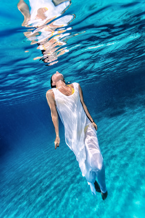 Beautiful female wearing white dress underwater, active lifestyle, diving in clear transparent water of sea, summer vacation concept