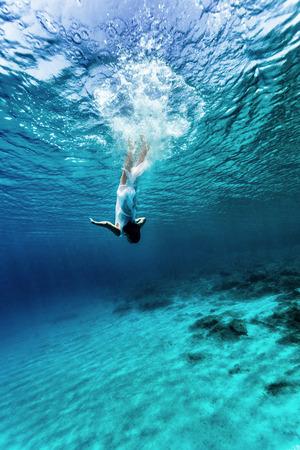 Aktív fiatal nő táncol a víz alatt, élvezi nyári vakáció kék átlátszó víz, merülés, hogy az alján tenger, élvezet és szabadság fogalmát