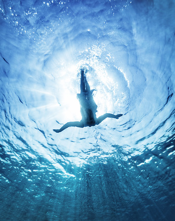 Active sportive woman diving in transparent blue sea in bright sunny day, enjoying summer vacation, refreshment concept