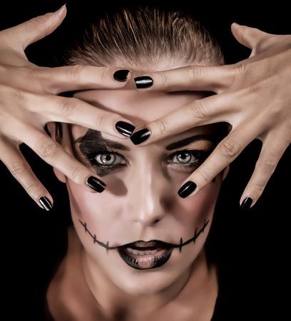 beldam: Closeup ritratto di moda mostro ragazza con le mani vicino al viso isolato su sfondo nero, il trucco aggressivo per la festa di Halloween