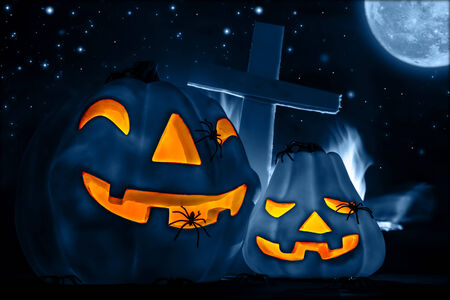 Scary glowing blue pumpkin decoration with creepy spider, burning fire, cross on the cemetery, Halloween fun, misterious holiday celebration photo