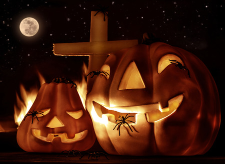 Creepy Halloween night, glowing carved pumpkin with scary horrible spiders, cross and burning flame on the graveyard in full moon night photo
