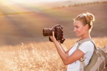 Happy photographer enjoying autumn nature, smiling traveler girl with camera in hands photographing golden dry wheat field in sun rays photo