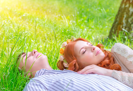 Young lovers resting outdoors, boyfriend and girlfriend lying down on fresh green grass with closed eyes, enjoying romantic relationship, love concept photo