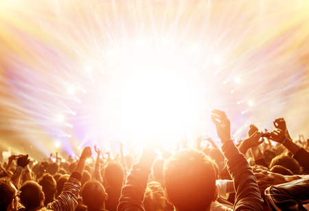 zábava: Aktivní šťastní lidé, kteří požívají rockový koncert, mnoho světla z jeviště, kde si hrají slavné hudební skupiny, noční zábava koncept