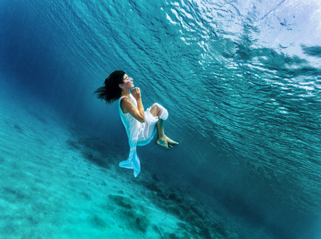 Happy girl dancing underwater, wearing stylish dress, luxury sea performance, active summer vacation, sport and art concept Stock Photo