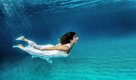 Happy girl swimming underwater, wearing stylish dress, luxury sea performance, active summer vacation, relaxation and enjoyment concept photo