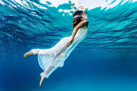 Nice girl emerges from the sea, swimming underwater, enjoying nice refreshing water, wearing long dress, summer vacation and travel concept photo