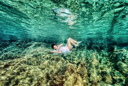 paz interior: Bailando bajo el agua, natación hermosa mujer joven en el mar cerca de un hermoso jardín de coral, estilo de vida activo, vacaciones de verano y concepto de vacaciones Foto de archivo