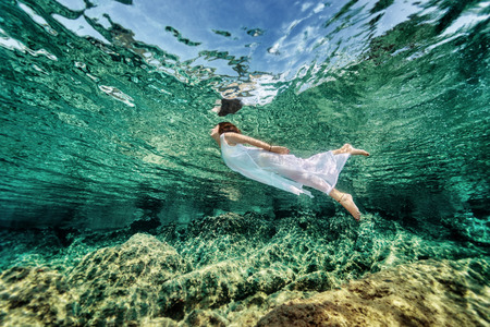 happy life: Swimming in transparent sea, emerges from clear sea, wearing fashionable white dress, luxury summer vacation, freedom and enjoyment concept