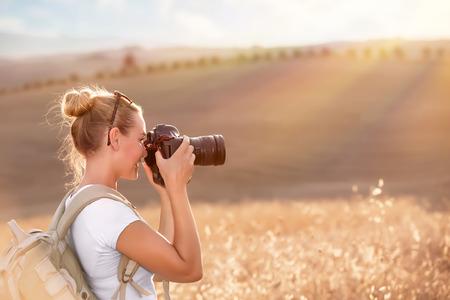 Happy traveler girl photographing ripe wheat field in bright sun rays, autumn harvest season, interesting profession, travel and tourism concept Archivio Fotografico