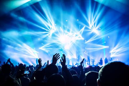 Große Gruppe von glücklichen Menschen genießen Rockkonzert, klatschen mit bis erhobenen Händen, blaue Lichter von der Bühne, neues Jahr Feier-Konzept