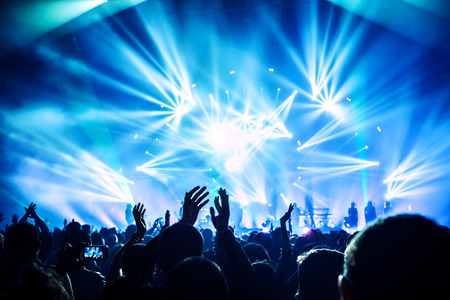 people partying: Large group of happy people enjoying rock concert, clapping with raised up hands, blue lights from the stage, new year celebration concept