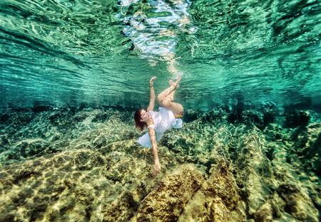 paz interior: Mujer activa con el placer de nadar bajo el agua, disfrutando de un hermoso jardín de coral, la relajación en el mar, concepto de las vacaciones de verano