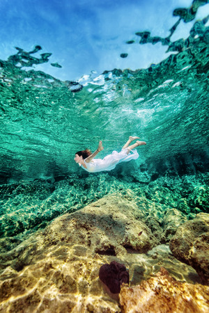 Woman swimming near rock in transparent blue sea, wearing white dress, relaxation in refreshing water, summer enjoyment concept photo