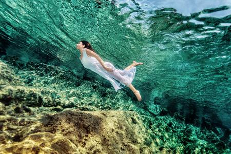 Frauenschwimmen in der Nähe von Stein in transparente blaue Meer, tragen weißes Kleid, Entspannung im erfrischenden Wasser, Sommerspaß Konzept Standard-Bild - 33424759