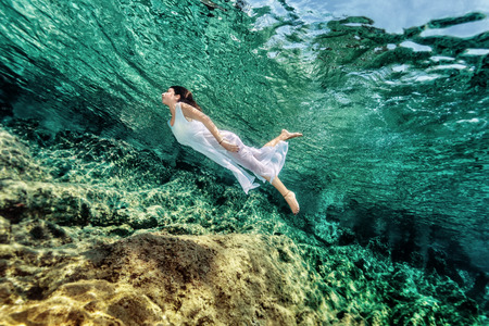 underwater sport: Woman swimming near rock in transparent blue sea, wearing white dress, relaxation in refreshing water, summer enjoyment concept