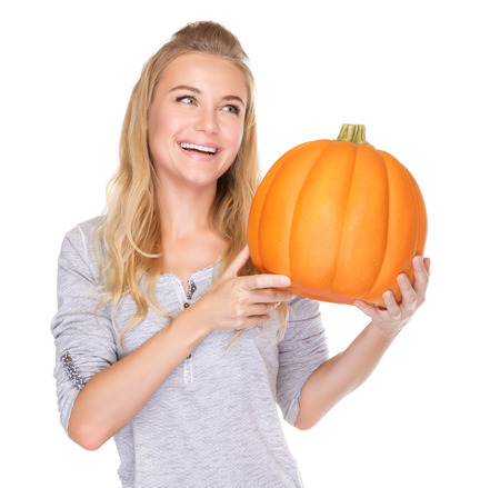 Portrait of happy woman with big ripe Thanksgiving pumpkin isolated on white background, harvest season concept photo