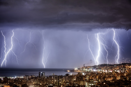 weather: Night cityscape with strong lightning, majestic view on coastal town in dark stormy night, dramatic skyscape with bright zipper Stock Photo