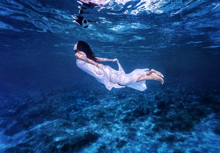 Zwemmen in prachtige blauwe zee, zachtaardige vrouw in witte mode jurk onder water duiken, verfrissing en genot begrip Stockfoto