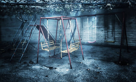 abandoned city: Old rusted playground, abandoned aged swings, destroyed childhood, damages in attraction park, war and poverty concept