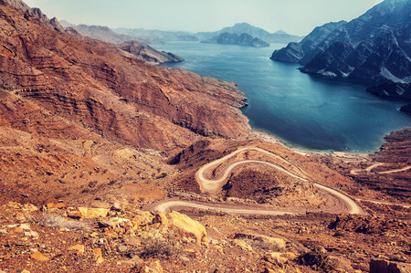 rocky road: Beautiful landscape, curve road in dry arabian mountains over sea, exotic travel to the arab country, travel and tourism concept Stock Photo