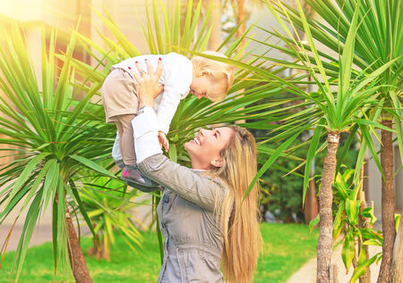 Cheerful mother playing with baby in fresh green palm park, smiling woman lifting up her cute little daughter, happy young family concept photo