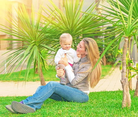 Young happy family having fun on backyard, mother with little daughter sitting on green grass and enjoying nice sunny day, love concept photo