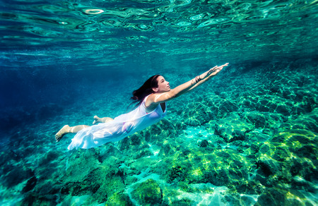 transparent dress: Refreshing swimming underwater, beautiful young woman wearing fashion white long dress and dive into clear transparent sea, luxury summer vacation concept Stock Photo