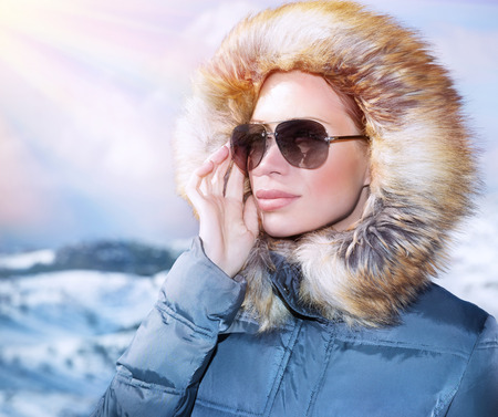 Luxury woman portrait in wintertime, wearing stylish sunglasses and warm coat with furry hood and looking away, winter fashion concept photo