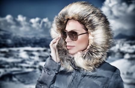 Grunge style photo of luxury woman portrait in wintertime outdoors, wearing stylish sunglasses and warm coat with furry hood and looking away, fashionable winter style concept photo