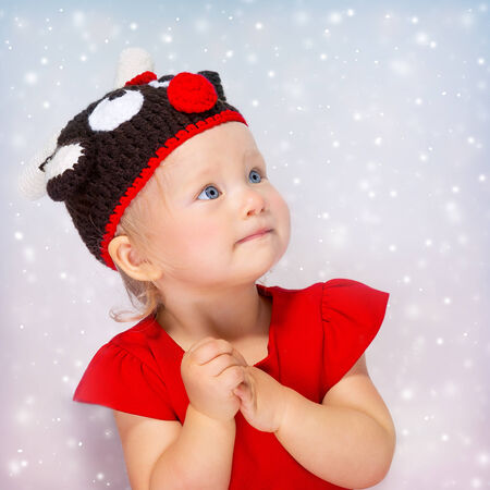 rudolf: Cute little girl portrait, sweet baby wearing Rudolf hat isolated on gray snowy background, Christmas celebration concept