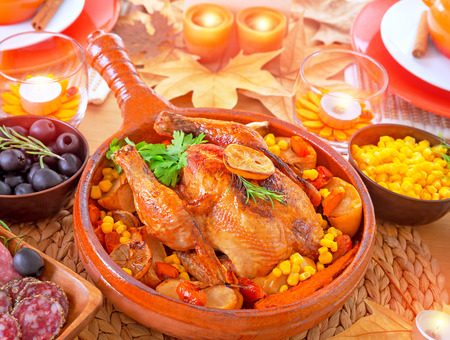 festive food: Thanksgiving day dinner, traditional festive food, tasty oven baked turkey with vegetables and lemon, beautiful decorated holiday table