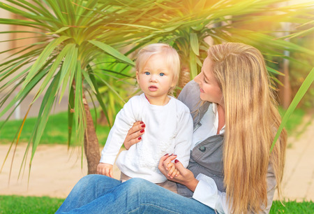 Happy mother with baby girl sitting on green field in tropical park in bright sunny day, enjoying motherhood, love and happiness concept photo