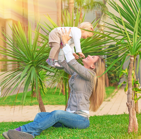 Happy young woman with pleasure playing outdoors with her cute little blond daughter, mother lifting up baby girl, having fun in the garden in sunny day, love and enjoyment concept photo