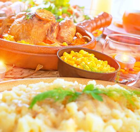 corn: Cena festiva con pollo al horno en pieza central de la tabla, celebraci�n de la fiesta de Navidad, diferente delicioso plato en festivo Foto de archivo