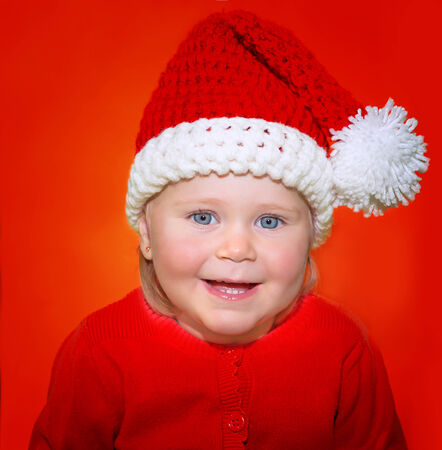 Portrait of cute little baby girl wearing Santa hat isolated on red background, funny festive costume for Christmas celebration photo