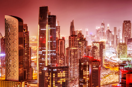 Beautiful background of Dubai at night, gorgeous cityscape over pink sky, many glowing lights of tall skyscrapers, luxury modern expensive architecture design Stock Photo