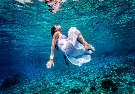 activities: Gorgeous female dancing underwater, wearing long white fashion dress, summer activity, relaxation in blue transparent sea, enjoyment and refreshment concept