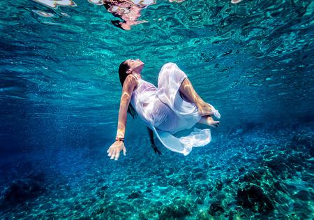 Gyönyörű nő táncol a víz alatt, fárasztó, hosszú fehér divat ruha, nyári tevékenység, pihenés kék átlátszó tengeri, élvezet és frissítő koncepció Stock fotó