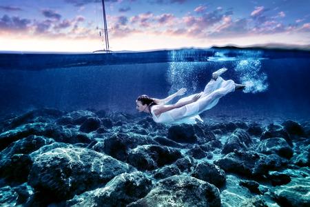 Jonge vrouw duiken in zonsondergang tijd, genietend van onderwater zwemmen, dragen lange witte jurk, luxe zomervakantie, vrijheid en plezier begrip Stockfoto
