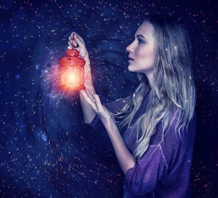 별이 빛나는 하늘 배경에 마술 랜 턴과 함께 아름 다운 여자 손을 잡고 빨간색 빈티지 램프, 골동품 축제 특성, 크리스마스 휴일 개념